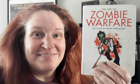 Carma holding a copy of The Art of Zombie Warfare