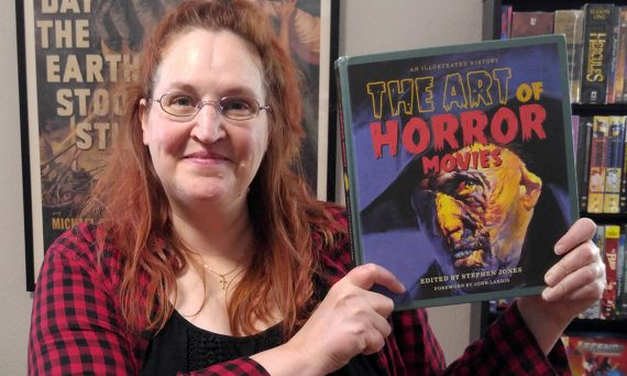 "Carma Spence holding a copy of ""The Art of Horror Movies"" by Stephen Jones"
