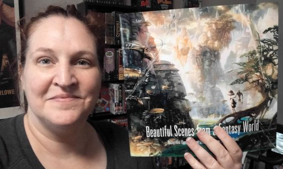 Carma Spence holding a copy of Beautiful Scenes from a Fantasy World