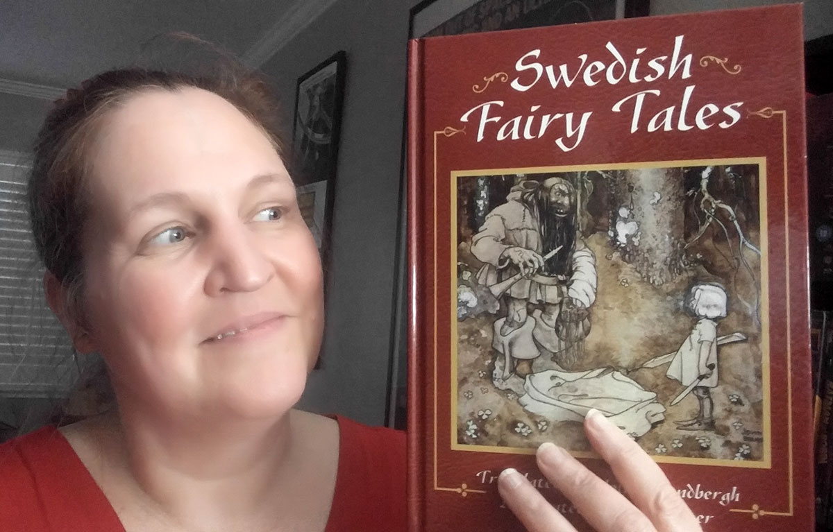 Carma Spence, The Genre Traveler, holding a copy of Swedish Fairy Tales