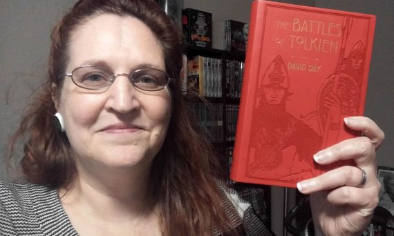 Carma Spence, The Genre Traveler, holding a copy of The Battles of Tolkien by David Day