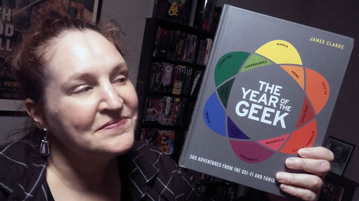 Carma Spence holding a copy of The Year of the Geek by James Clarke