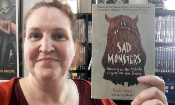 Carma Spence holding a copy of Sad Monsters by Frank Lesser