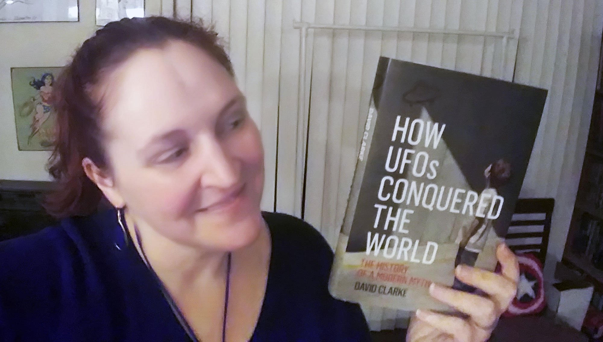 Carma holding a copy of How UFOs Conquered the World