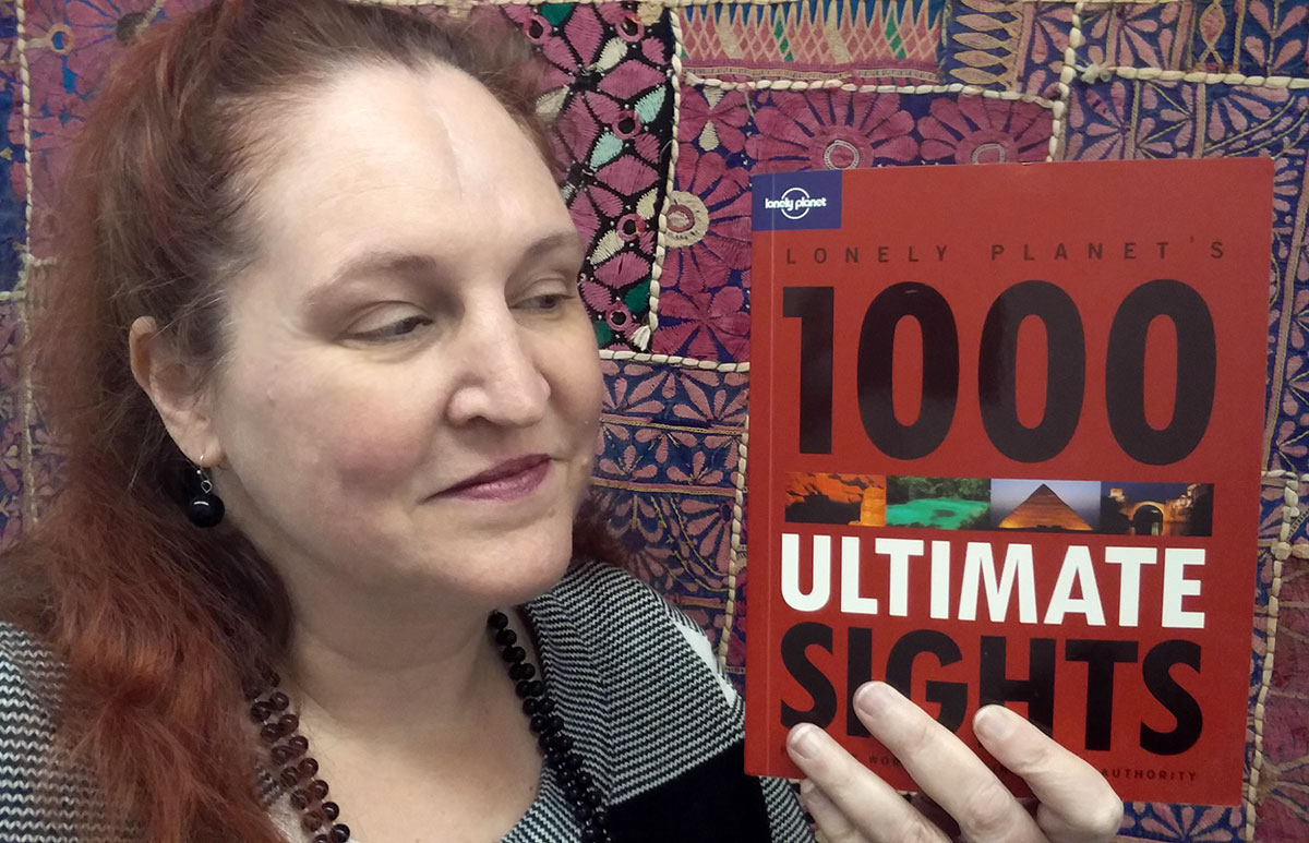 Carma holding a copy of Lonely Planet's 1000 Ultimate Sights