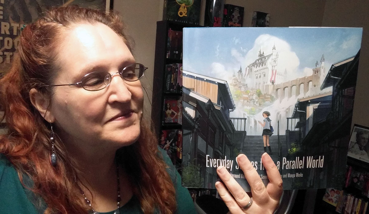 Carma Spence holding a copy of Everyday Scenes from a Parallel World