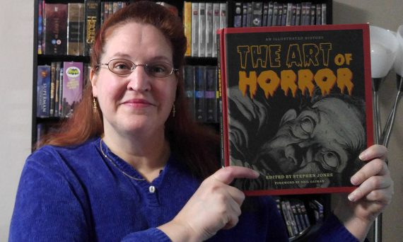 Carma holding a copy of The Art of Horror by Stephen Jones