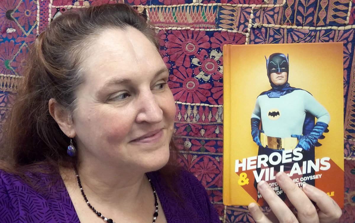 Carma holding a copy of Heroes & Villains by Andrew Boyle