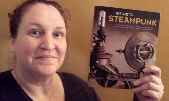 Carma holding a copy of The Art of Steampunk