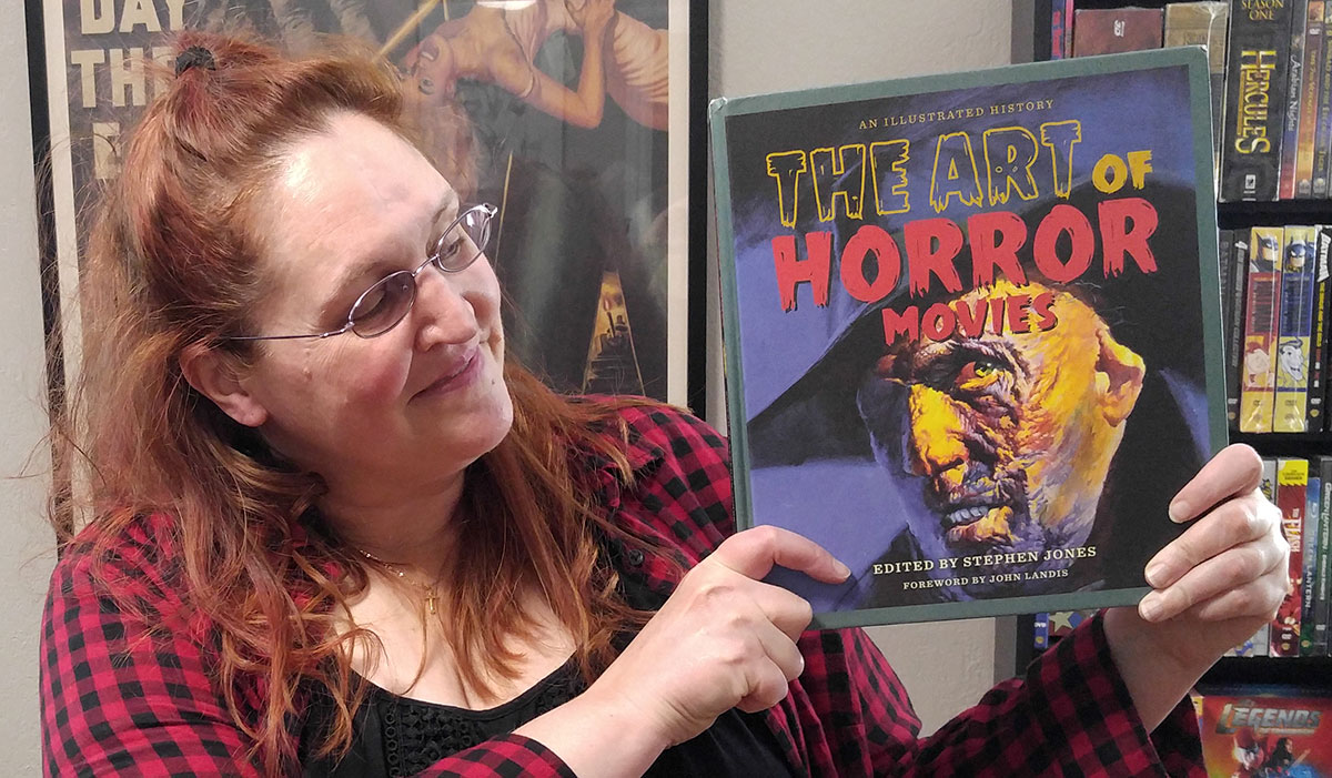 """Carma Spence holding a copy of """"The Art of Horror Movies"""" by Stephen Jones"""