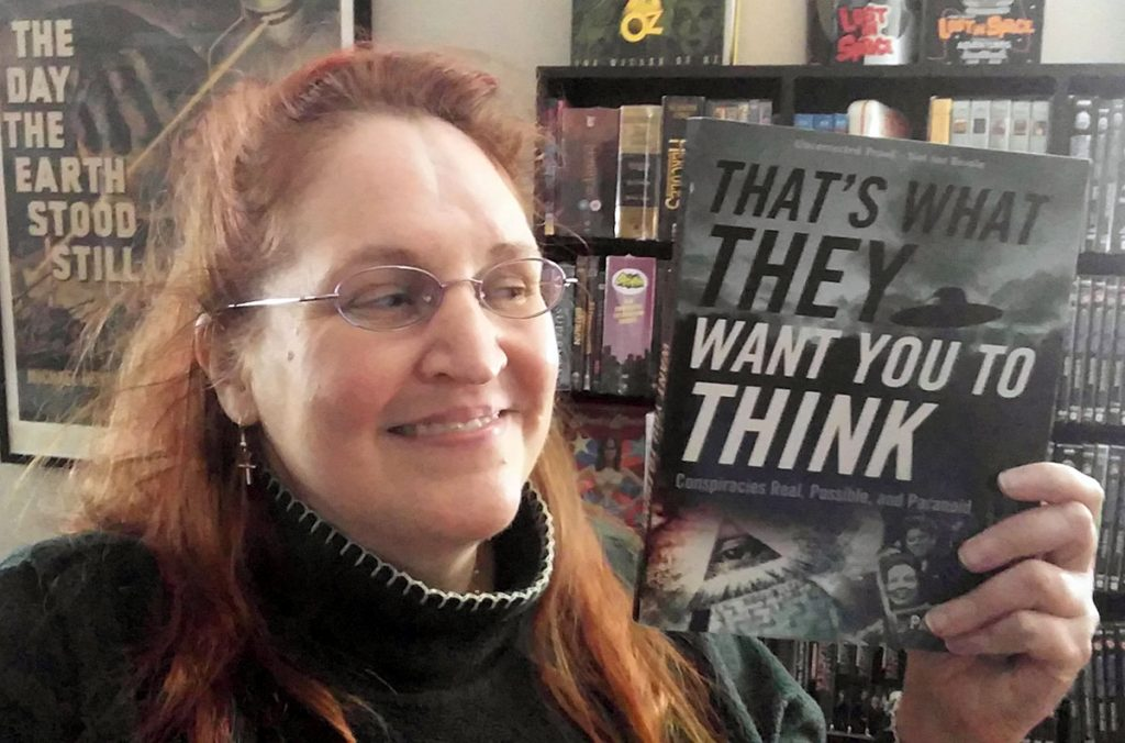 """Carma Spence holding a copy of """"That's What They Want You to Think"""" by Paul Simpson"""
